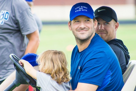 Tony Romo and his son, Rivers (2), wait on the rain on a golf cart. (Photo by Dan Garcia/The Early Registration)
